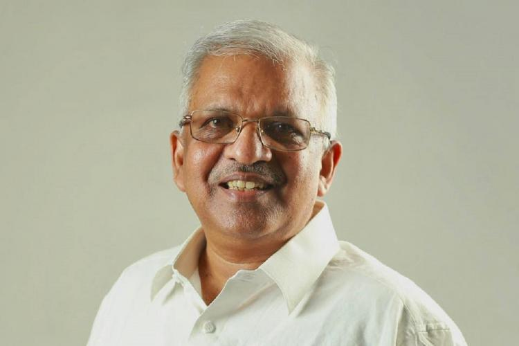 Jayarajan in white shirt specs white hair smiles at the camera an offwhite background behind him