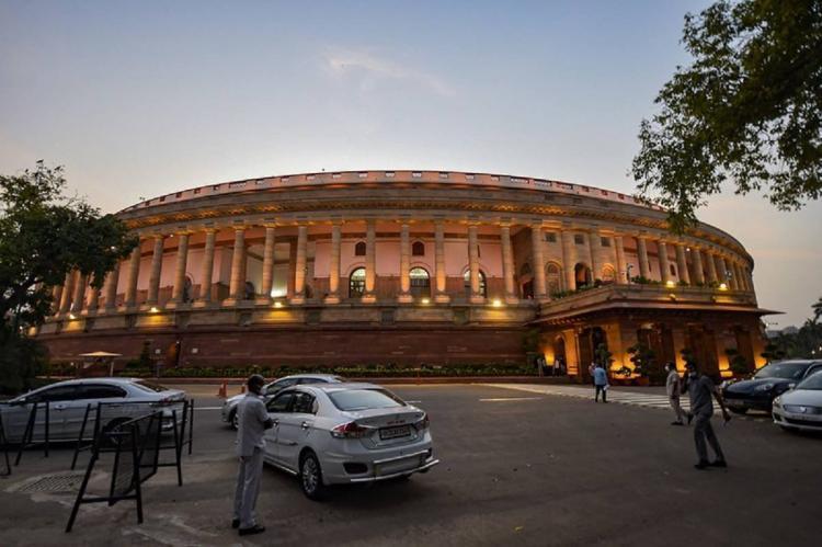Parliament building at dusk, cars parked at entrance