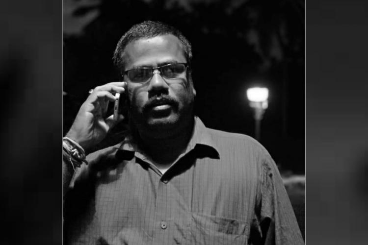 Black and white image of journalist Parthasarathy talking on the phone