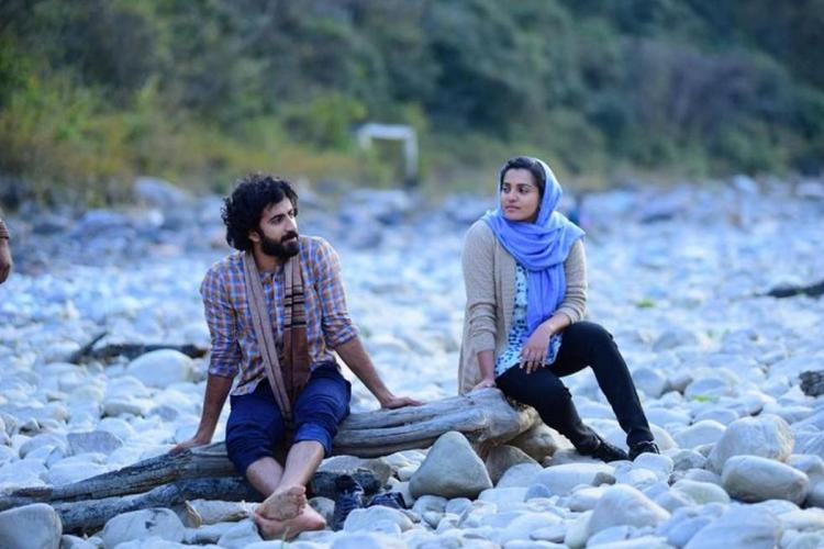 Roshan sits on a branch and Parvathy with a sweater and a shawl around her head sits nearby in a place filled with white stones