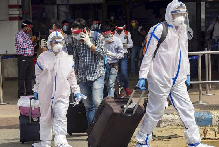 Passengers in PPE and masks walking out of airport