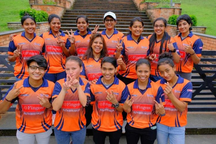 13 girls in orange jerseys stand in rows with thumbs up signs