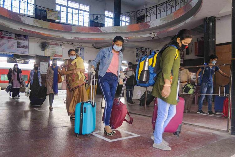 People at a railway station in Patna are seen walking through with luggage masks and physical distancing norms