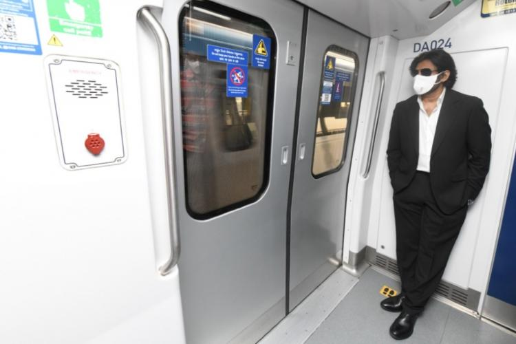Pawan Kalyan in a black suit and white shirt wearing a white face mask and dark shades standing by the doors of the metro
