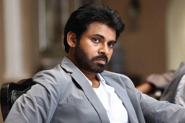 Pawan Kalyan in a grey suit and white shirt looking seriously to his right at the camera