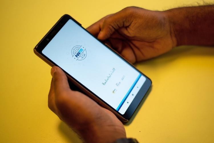 Person using the Paytm app on a phone hands resting on a yellow table only hands and phone in picture