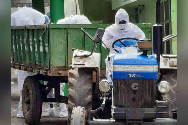 Dr Srinivasa Sriram driving a tractor in PPE suit to ferry body of a patient who succumbed to COVID-19 in Peddapalli District