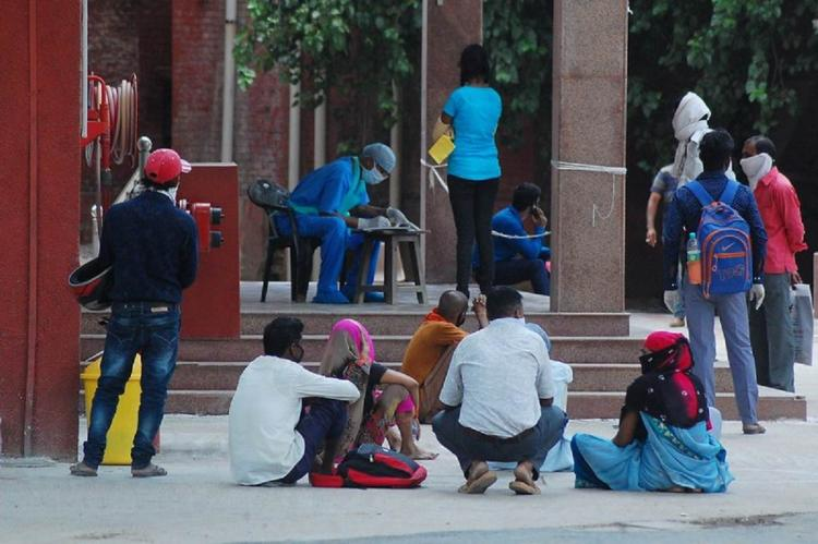 People sitting outside a station in Kanpur during COVID