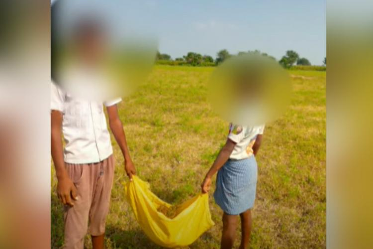 Two boys carrying a sack of excrement as instructed by the youngsters