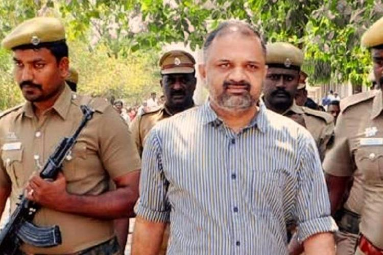 Perarivalan in a striped shirt led by policemen with guns