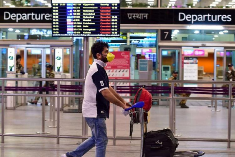 A passenger pushes his luggage past the entry gates of Bengaluru airport