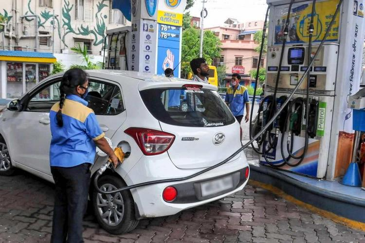 An employee fills in a vehicle at a filling station