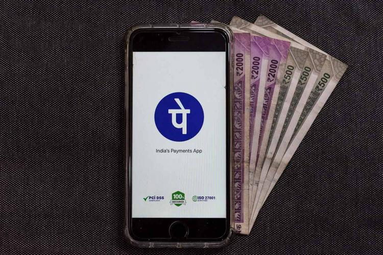 PhonePe open on a smartphone with a stack of Rs 2000 notes fanned out below it