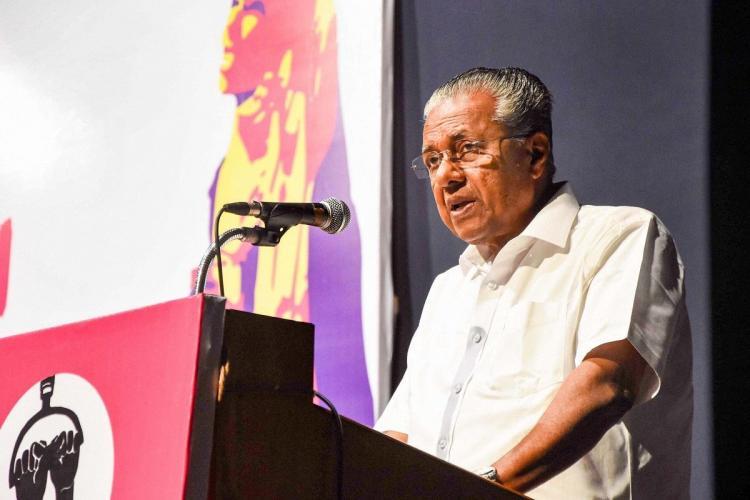 Kerala CM Pinarayi Vijayan standing speaking into a mic He is wearing a white shirt