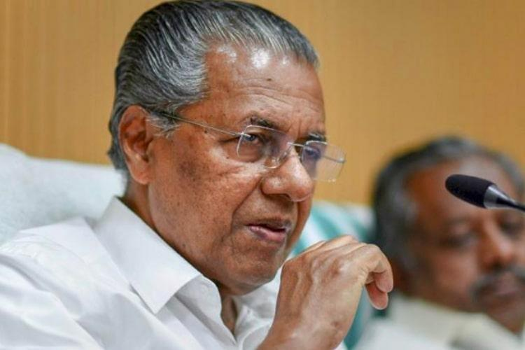 Pinarayi Vijayan in front of a mike addressing a press conference