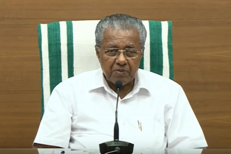 Kerala Chief Minister Pinarayi Vijayan addressing media sitting in a chair