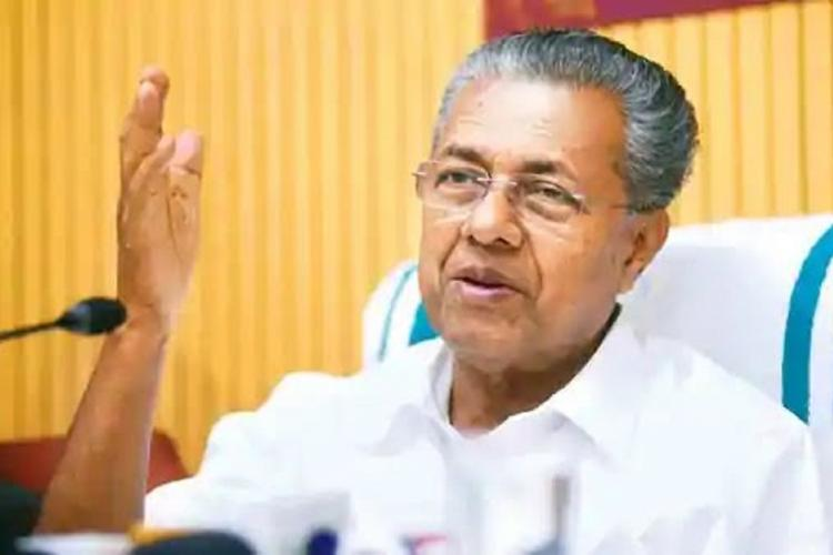 Kerala Chief Minister Pinarayi Vijayan facing a mike sitting in a chair