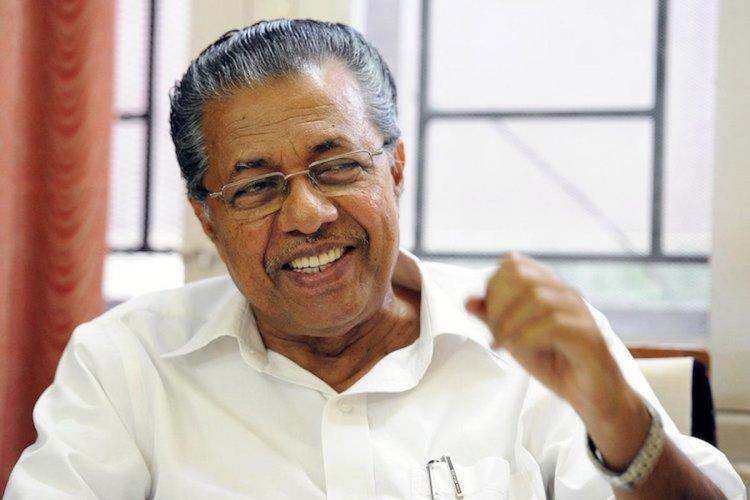 Pinarayi Vijayan wearing white shirt and laughing