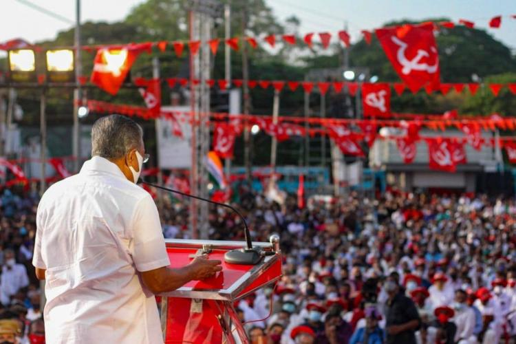 Pinarayi Vijayan addresses a huge gathering of people some of whom are holding up the CPIM party flags