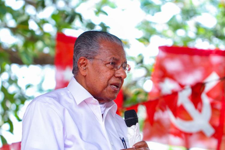 Pinarayi's side profile, in which he is speaking with a microphone in an open area, and in the background red Communist flags can be seen