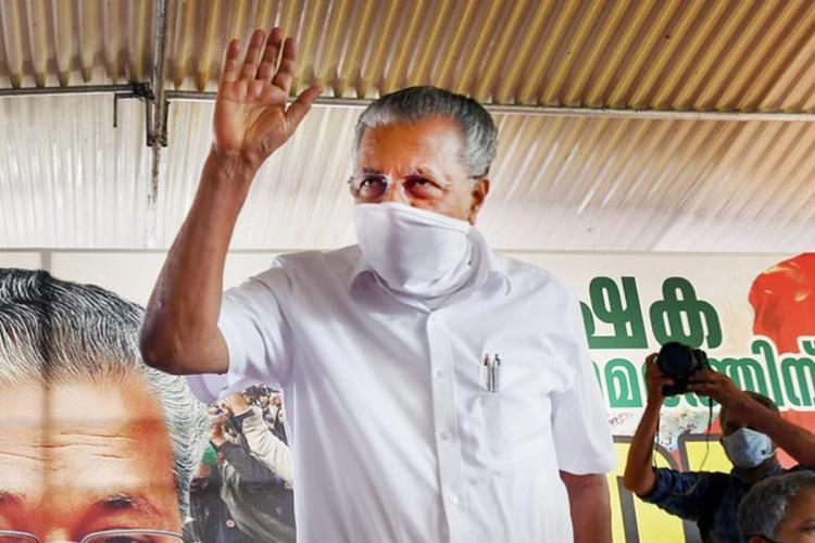 Kerala Chief Minister Pinarayi Vijayan wearing a white mask standing and waving