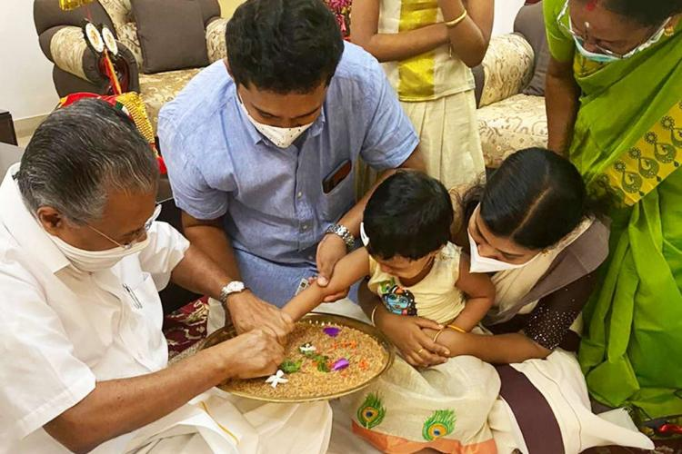Pinarayi Vijayan can be seen helping a little girl write her first letters on a platter of rice as she sits on her mothers lap A man in blue shirt is in between