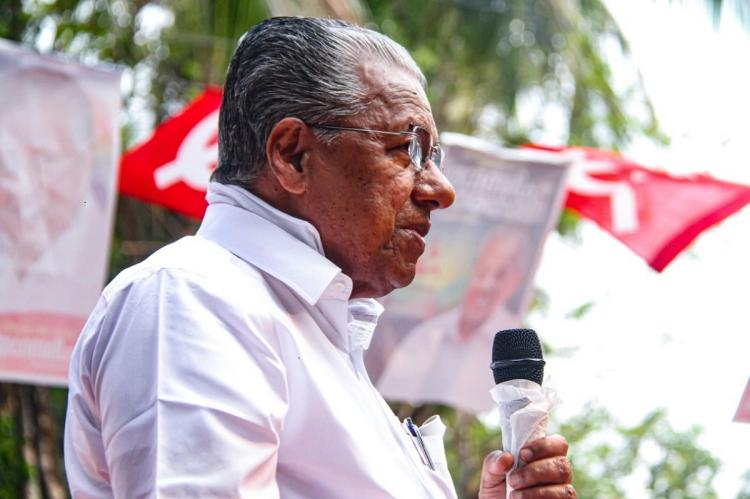 Kerala Pinarayi Vijayan standing and speaking at an Assembly election rally holding a mike against the background of a red flag