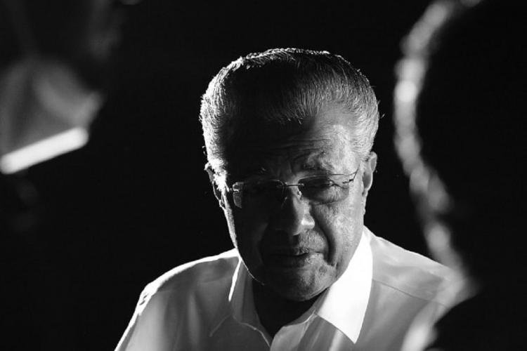 Black and white image of Pinarayi Vijayan in his white shirt and specs looking at someone who is facing him