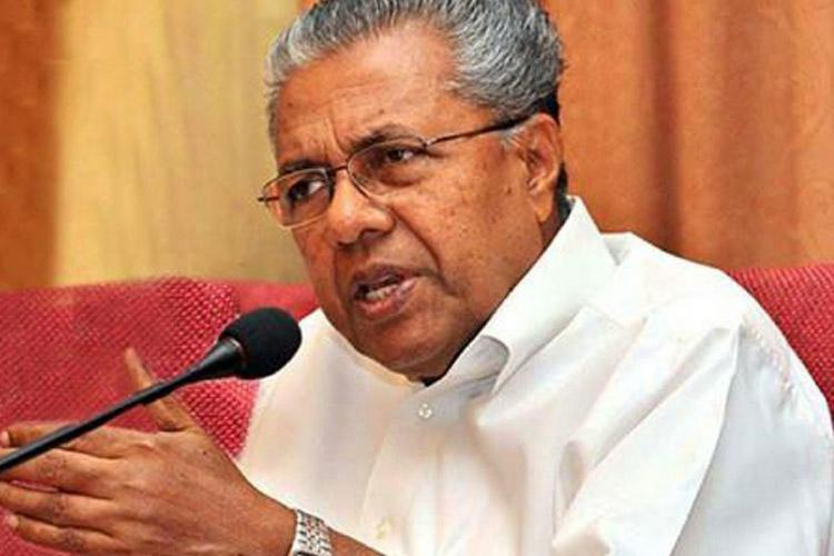 Pinarayin white shirt speaks in front of a microphone and the background has a mustard curtain