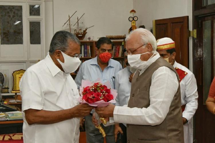 Governor Arif offers a bunch of red flowers to Pinarayi Vijayan both men are masked And behind them are two other men