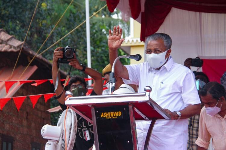 Kerala CM Pinarayi Vijayan addressing a poll rally waving wearing mask standing in front of a mic