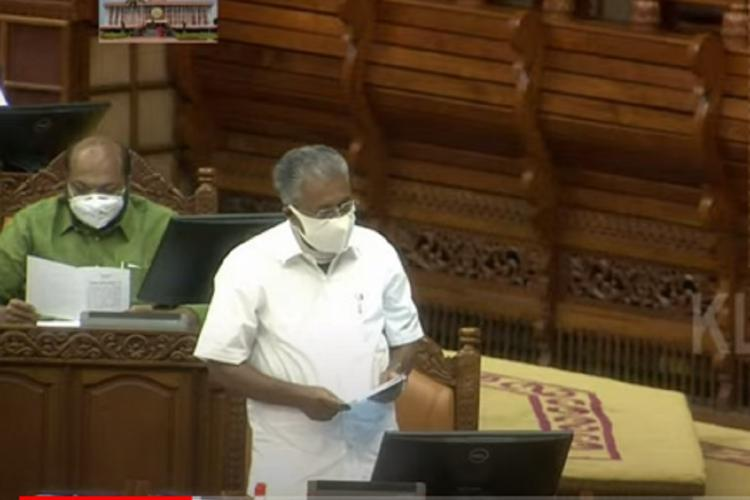 Pinarayi Vijayan stands up in Assembly wearing white and mask and reads the resolution and in the back you can see P Rajeev sit