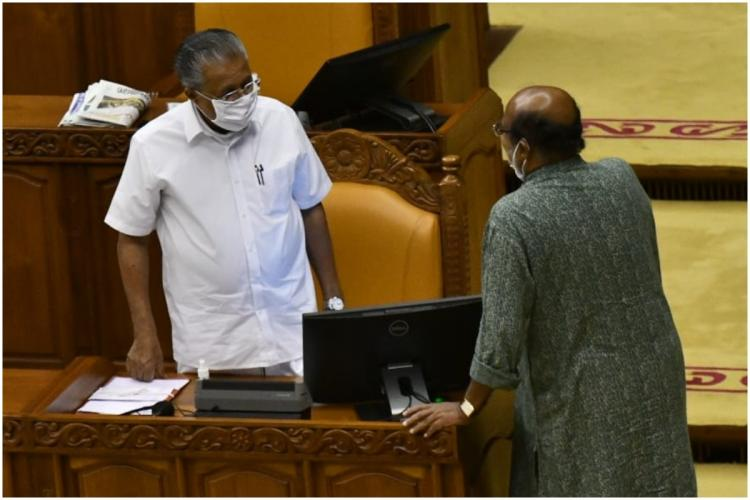 Kerala Chief Minister Pinarayi Vijayan and Finance Minister Thomas Isaac standing and facing each other in the Assembly