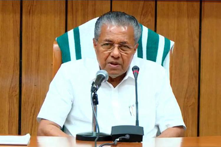 Pinarayi Vijayan sitting in his office chair in front of two microphones and speaking