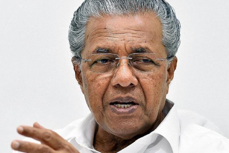 Pinarayi in white shirt speaks with one hand gesturing