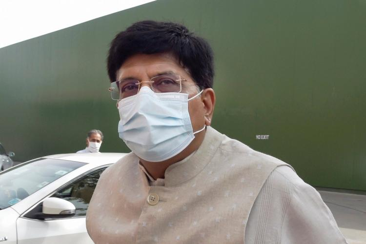 Piyush Goyal wearing a mask a light coloured suit and behind him is a long green fence and a car
