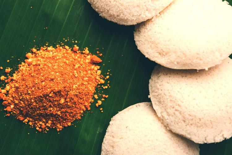 A banana leaf plate with idlis and a mound of south Indian podi