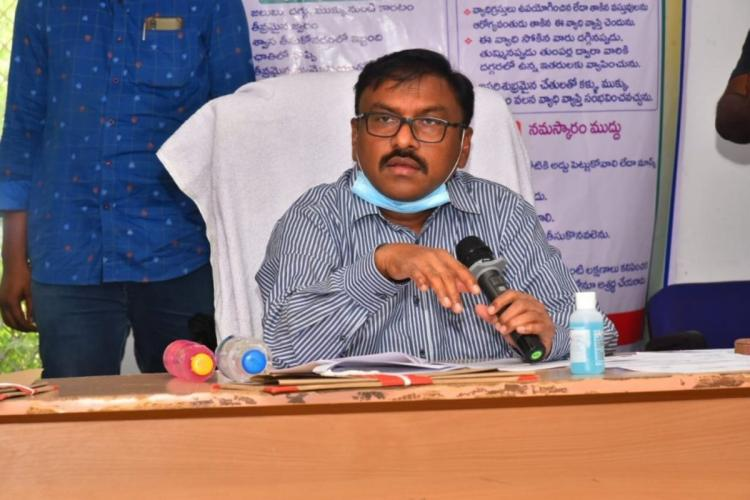 Prakasam District Collector Pola Bhaskar wearing a mask and speaking into a mic