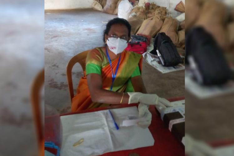 Polling officer wearing mask with CPIM symbol sitting inside polling booth