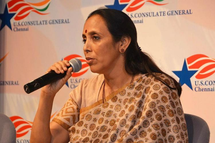 Poongothai Aladi Aruna seated and speaking into a mic She is wearing a beige saree and her hair is left loose at the back