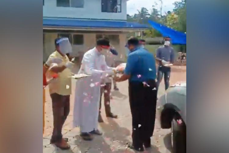 Parish priest of Poonthura presents bouquet to health workers coming to do COVID-19 test