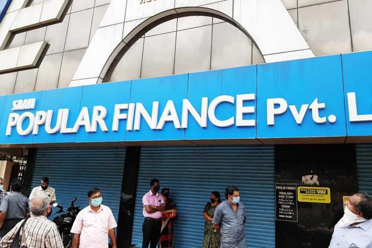 Customers waiting outside a shut outlet of Popular Finance in Kerala