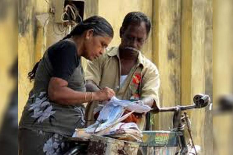 File image of a postman delivering a post and a woman signing it to receive