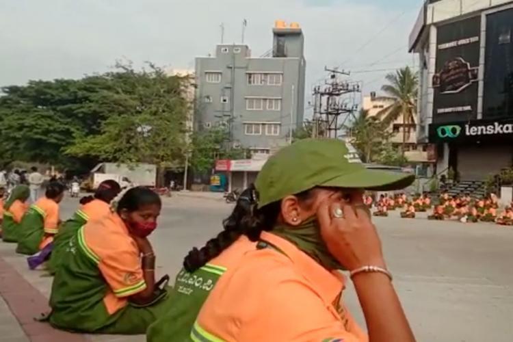 Pourakarmikas sitting on the roadside in protest in Bengalurus Banaswadi