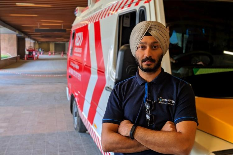 Prabhdeep Singh wearing a blue company t-shirt and a cream-coloured turban standing with folded hands and looking at the camera in front of a Red ambulance