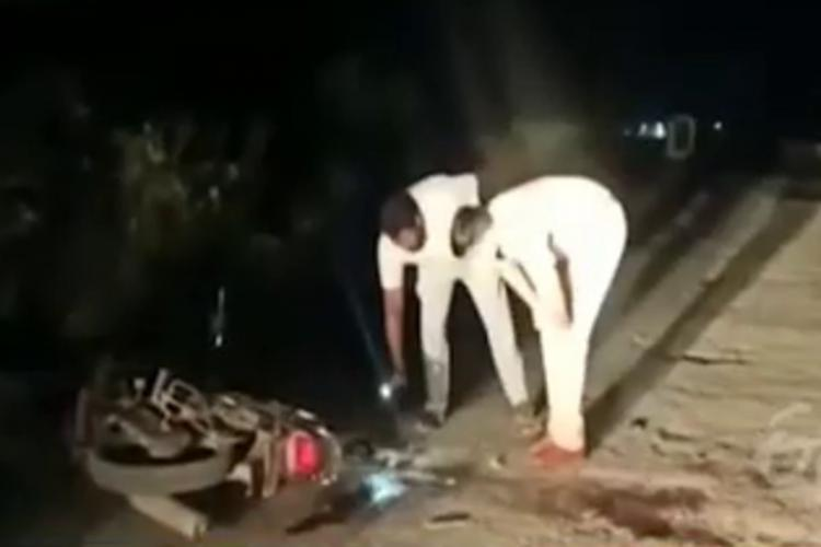 Prakasam police investigation the location where two TDP workers were attacked two policemen are bent over with a torch looking at the blood stains around the vehicle