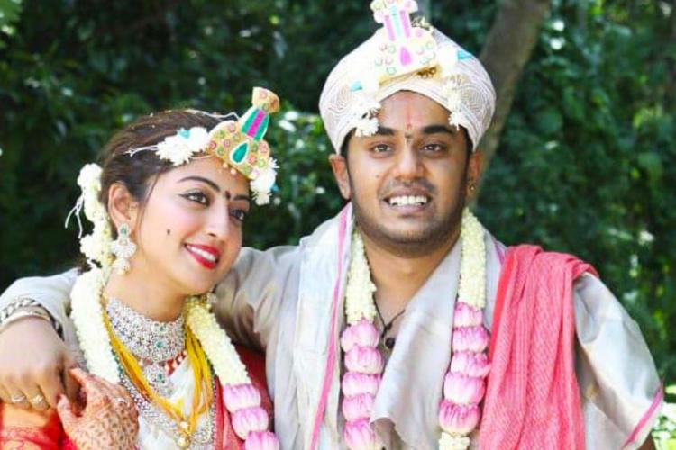 Pranitha is seen wearing a white saree with red borders and Her husband Nitin seen with his arm around her shoulder and is wearing a festive dhoti in the image
