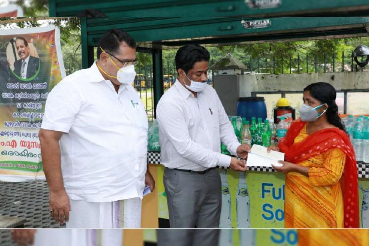 Lulu group's officials handing over money to Prasanna