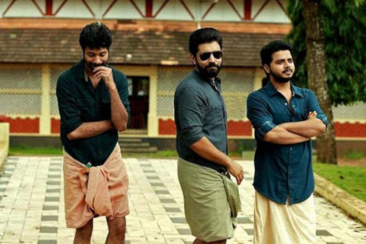 Still from Malayalam movie Premam showing three actors including Nivin Pauly clad in multi coloured lungi