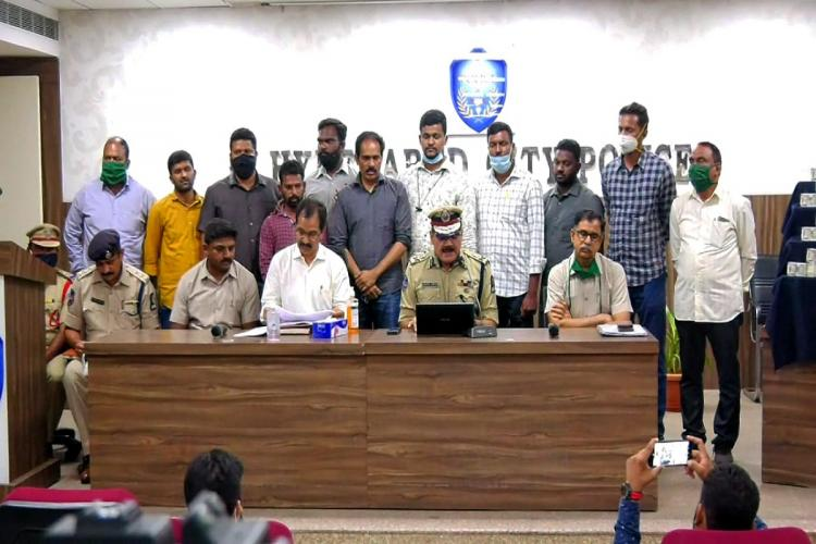 Police officials including accused and others were posing for a picture while the Commissioner is addressing a pressmeet in his uniform